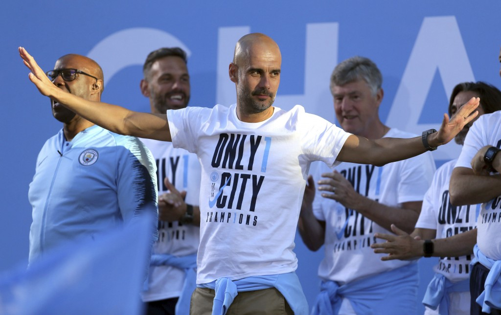 Manchester City soccer team manager Pep Guardiola acknowledges supporters during the British Premier League champions trophy parade in Manchester, Eng
