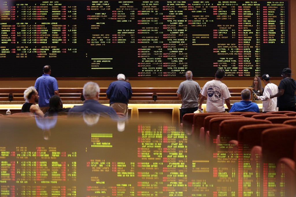 People line up to place bets in the sports book at the South Point hotel-casino, Monday, May 14, 2018, in Las Vegas. The Supreme Court on Monday gave