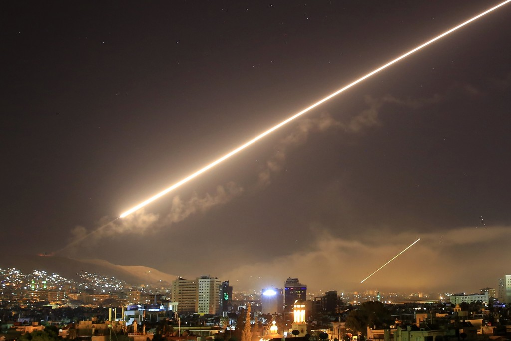 FILE - In this April 14, 2018 file photo, Damascus skies erupt with surface to air missile fire as the U.S. launches an attack on Syria targeting diff