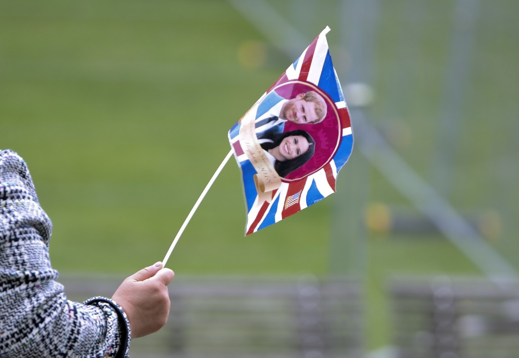A tour guide leads her group of tourists using a flag with the faces of Britain's Prince Harry and his fiance Meghan Markle in Windsor, England, Wedne