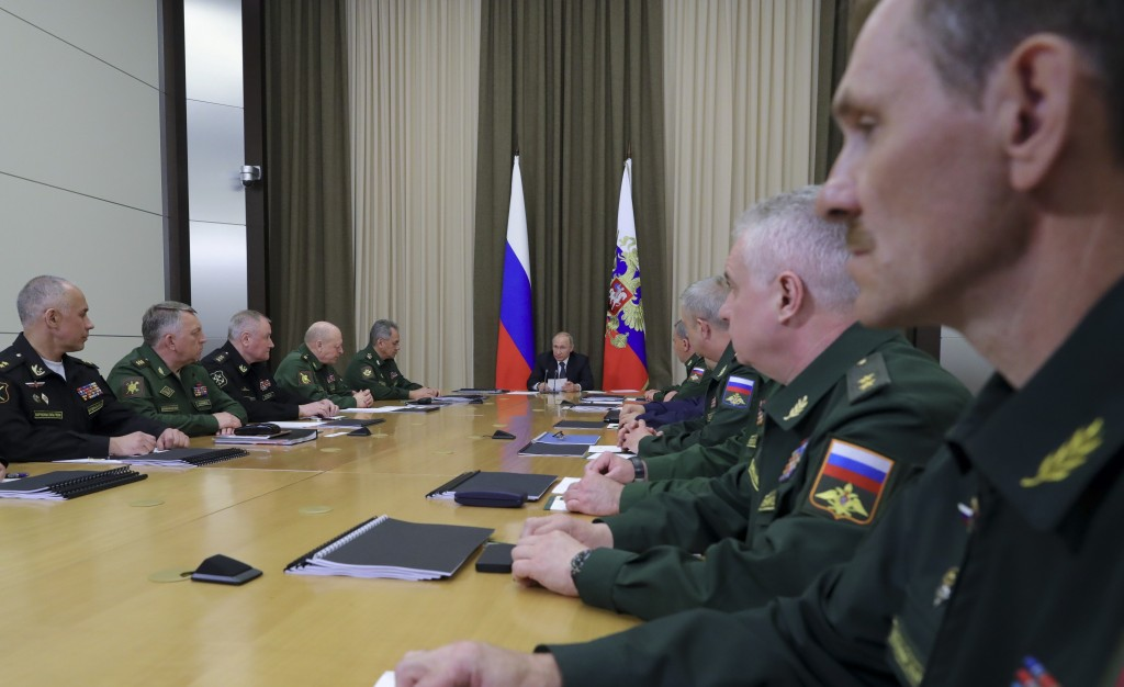 Russian President Vladimir Putin, background center, leads a meeting with the top military brass in the Bocharov Ruchei residence in the Black Sea res...