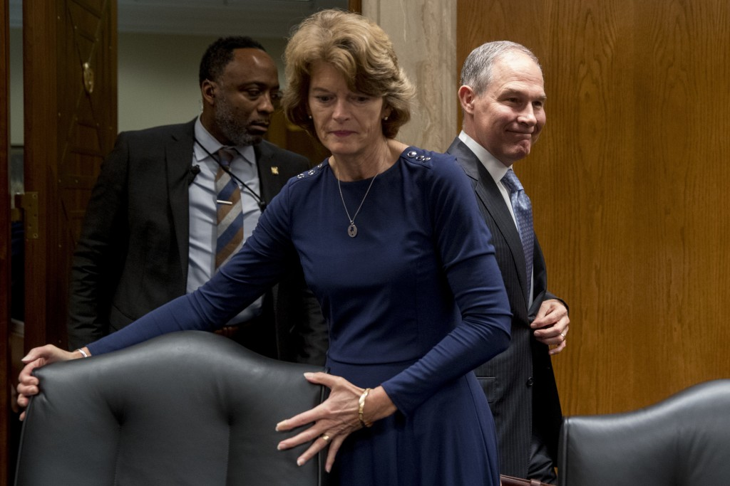 Environmental Protection Agency Administrator Scott Pruitt, accompanied by Chairman Lisa Murkowski, R-Alaska, center, and a member of his security, le