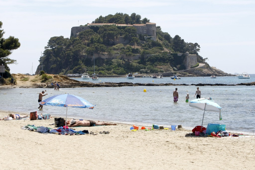 FILE - In this July 1, 2014 file photo, people bathe in front of the Fort de Bregancon, which has been the holiday retreat of French presidents for de