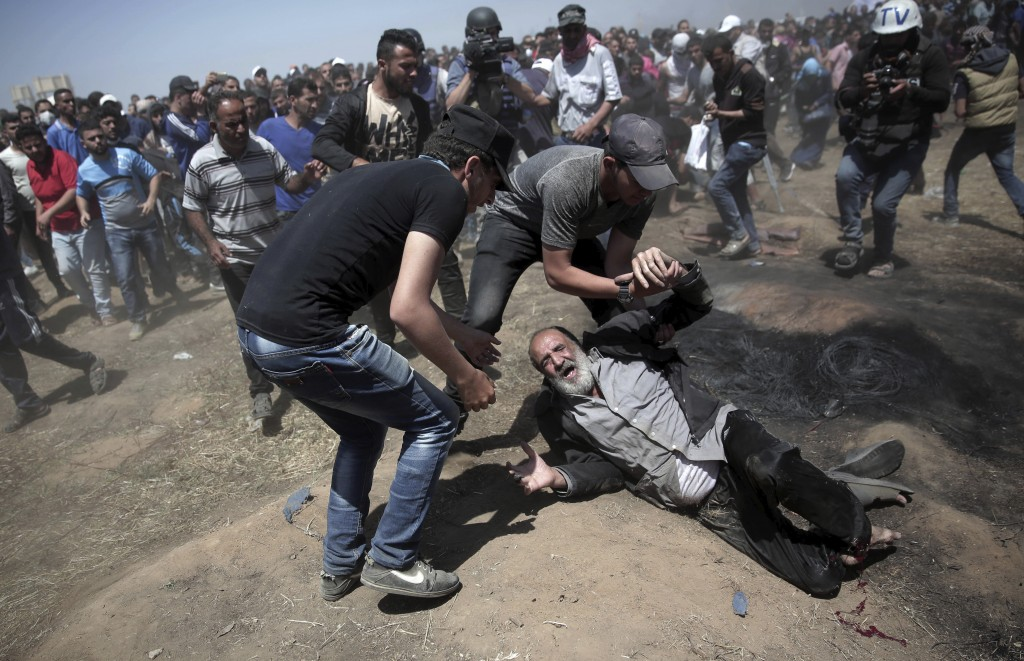FILE - In this May 14, 2018 file photo, an elderly Palestinian man falls on the ground after being shot by Israeli troops during a deadly protest at t...