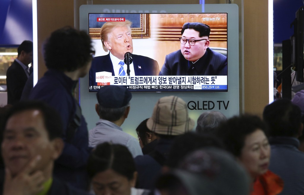 People watch a TV screen showing file footage of U.S. President Donald Trump, left, and North Korean leader Kim Jong Un during a news program at the S