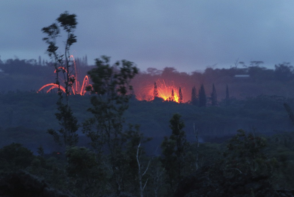 Lava shoots into the night sky from active fissures on the lower east rift of the Kilauea volcano, Tuesday, May 15, 2018, near Pahoa, Hawaii. (AP Phot...