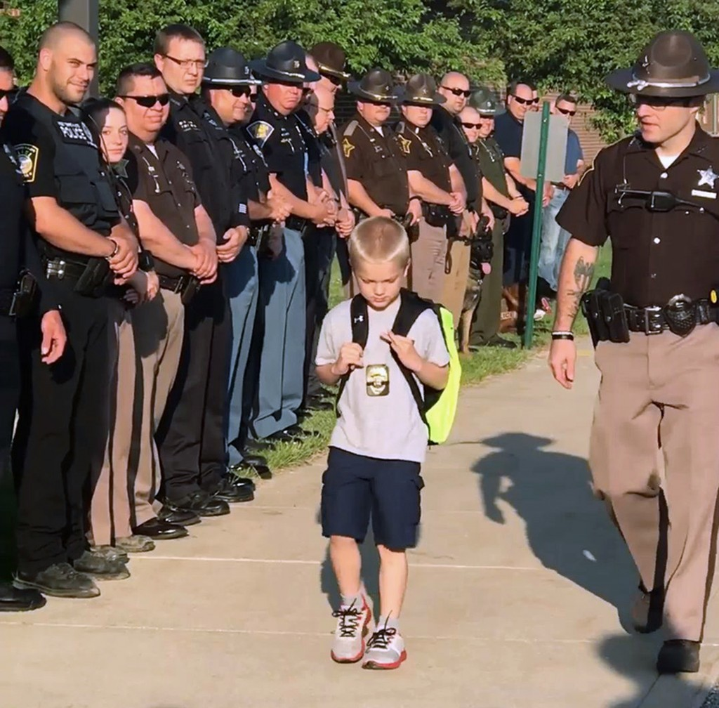 In this Monday, May 14, 2018, photo from a video provided by Samantha Phegley, police officers from multiple counties line up outside Sullivan Element