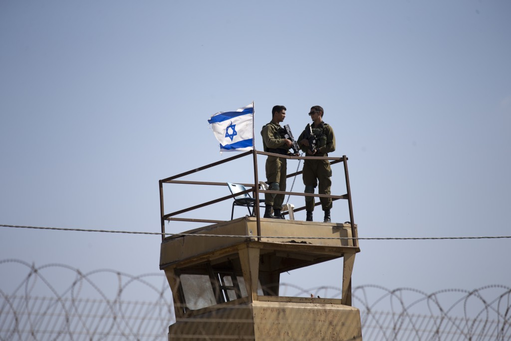 FILE - In this Tuesday, May 15, 2018 file photo, Israeli soldiers guard on top of a watch tower in a community along the Israel- Gaza Strip Border. Th