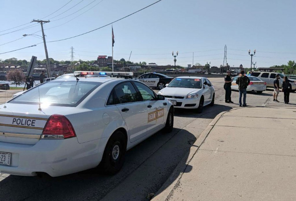 Police cars appear outside Dixon High School Wednesday, May 16, 2018 in Dixon, Ill. Officials say a police officer has shot and wounded a gunman at a