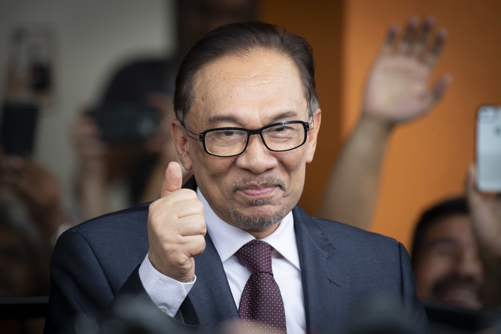 In this Wednesday, May 16, 2018, file photo, Malaysia's jailed opposition icon Anwar Ibrahim reacts to supporters as he leaves a hospital in Kuala Lum