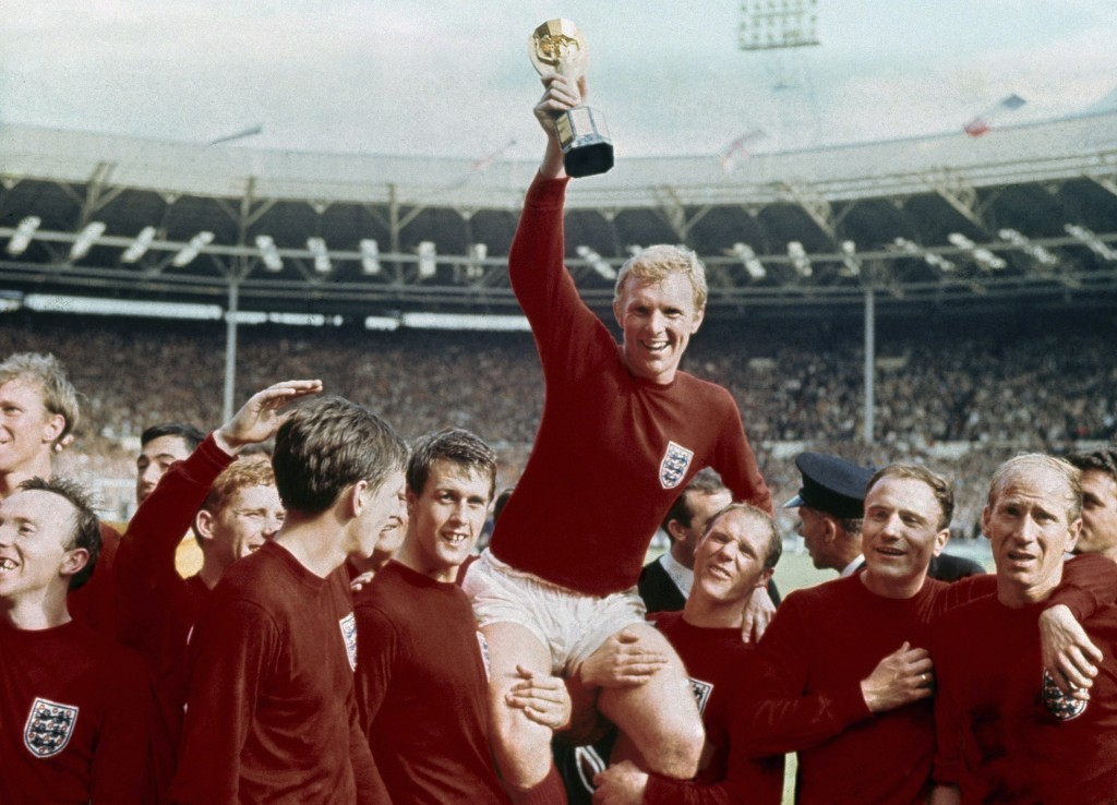 FILE - In this July 30, 1966 file photo, England's soccer captain Bobby Moore, center, is carried by teammates Geoff Hurst, center left, and Ray Wilso