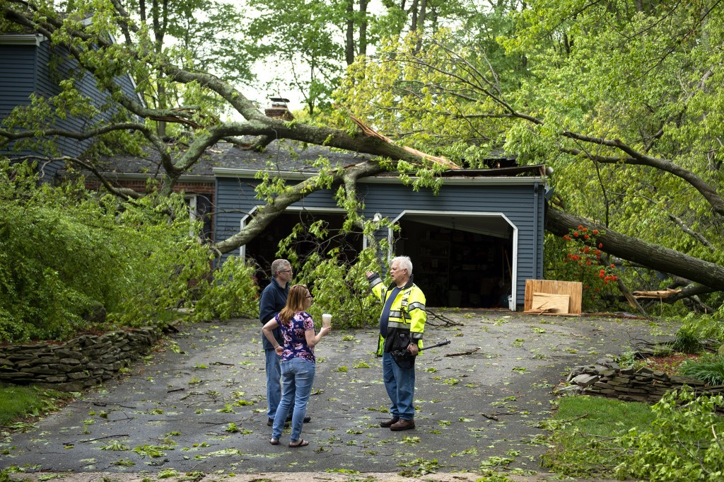 Chris Fletcher,left, and his wife Noel survey the storm damage to their home in Cheshire with a Cheshire volunteer firefighter on Wednesday, May 16, 2
