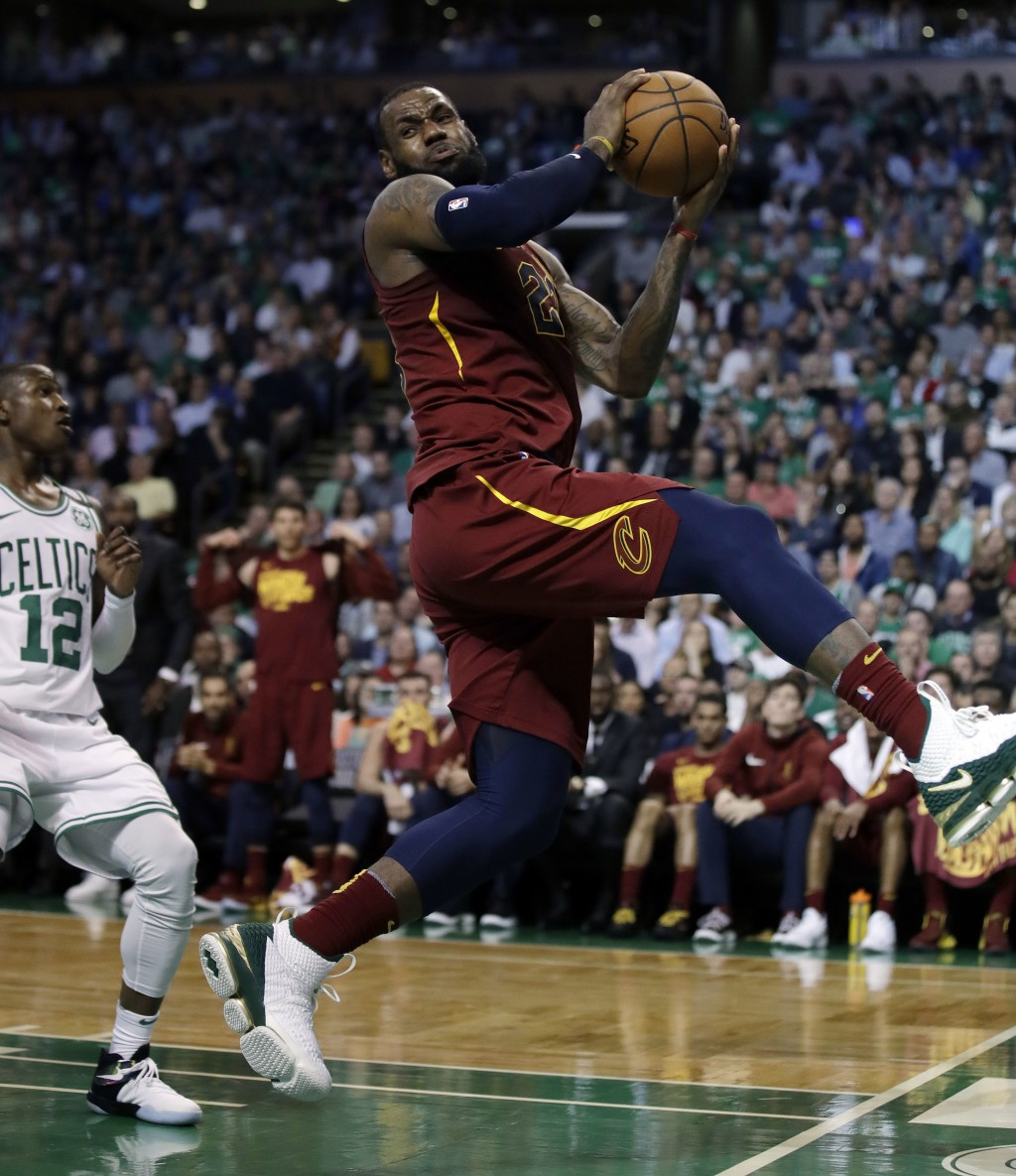Cleveland Cavaliers forward LeBron James recoils after colliding with Boston Celtics forward Jayson Tatum, out of picture, in front of Celtics guard T