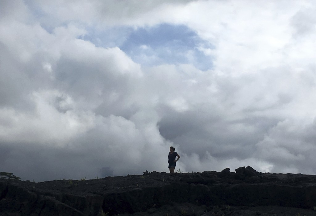 Tommie Joy Higgins of Hawaiian Paradise Park, Hawaii, stands on an old lava flow from 2014 as she watches plumes of volcanic gases rise from nearby ac...