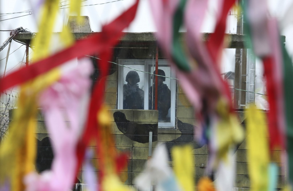 In this Wednesday, May 16, 2018, file photo, South Korean army soldiers stand guard inside a military guard post as ribbons hanging on a wire fence wi