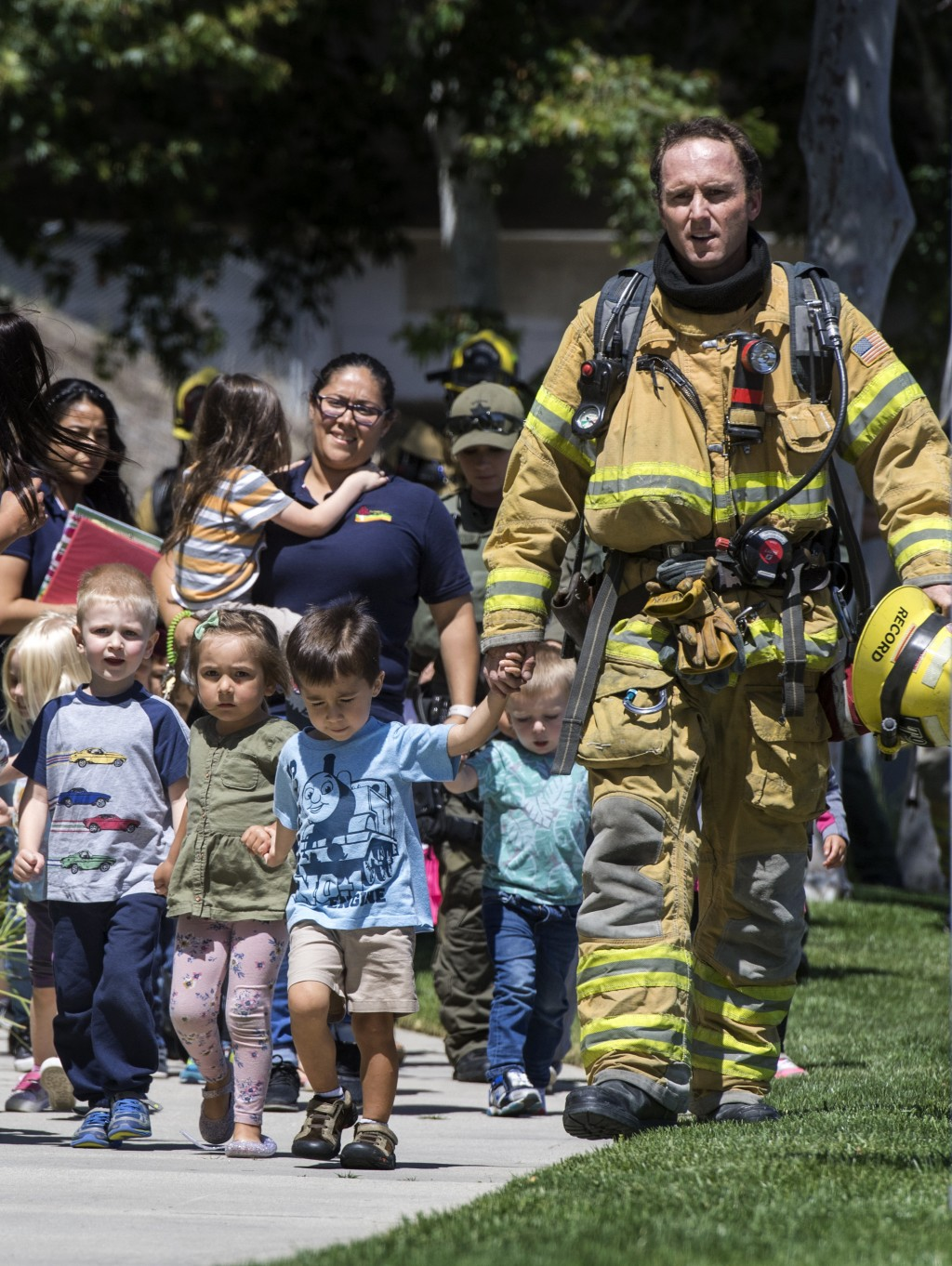 Firefighters and sheriff's deputies escort children from Academy on the Hill pre-k school in Aliso Viejo, Calif., on Tuesday, May 15, 2018, after a fa