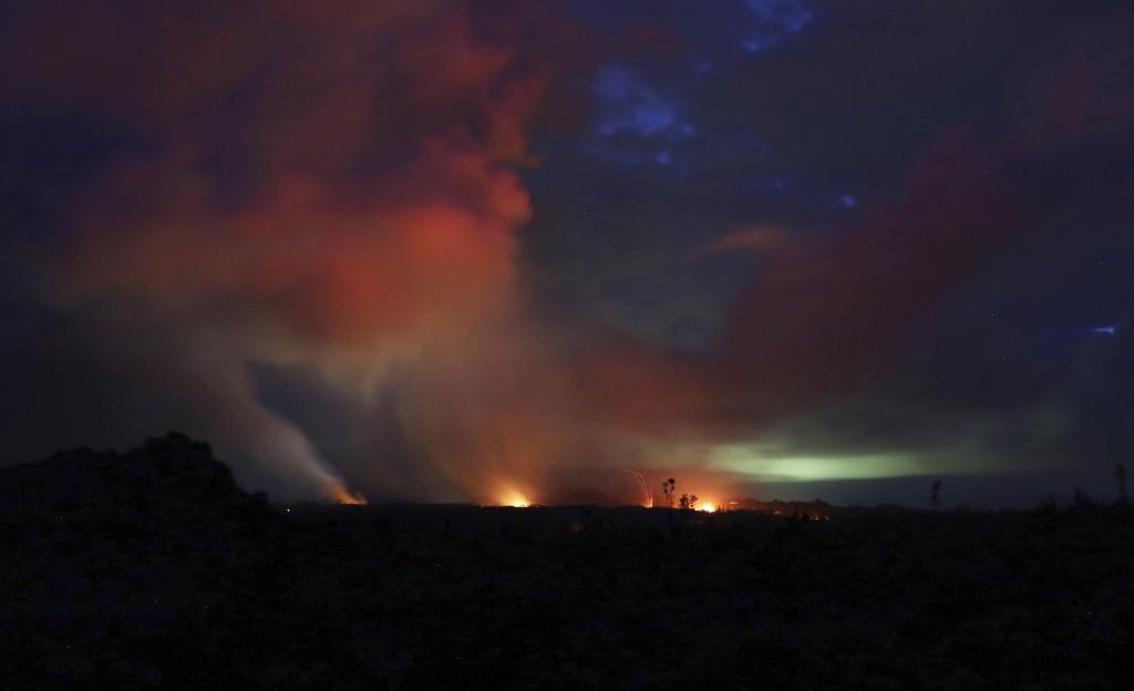 Lava shoots into the night sky from active fissures on the lower east rift of Kilauea volcano, Tuesday, May 15, 2018 near Pahoa, Hawaii. (AP Photo/Cal...