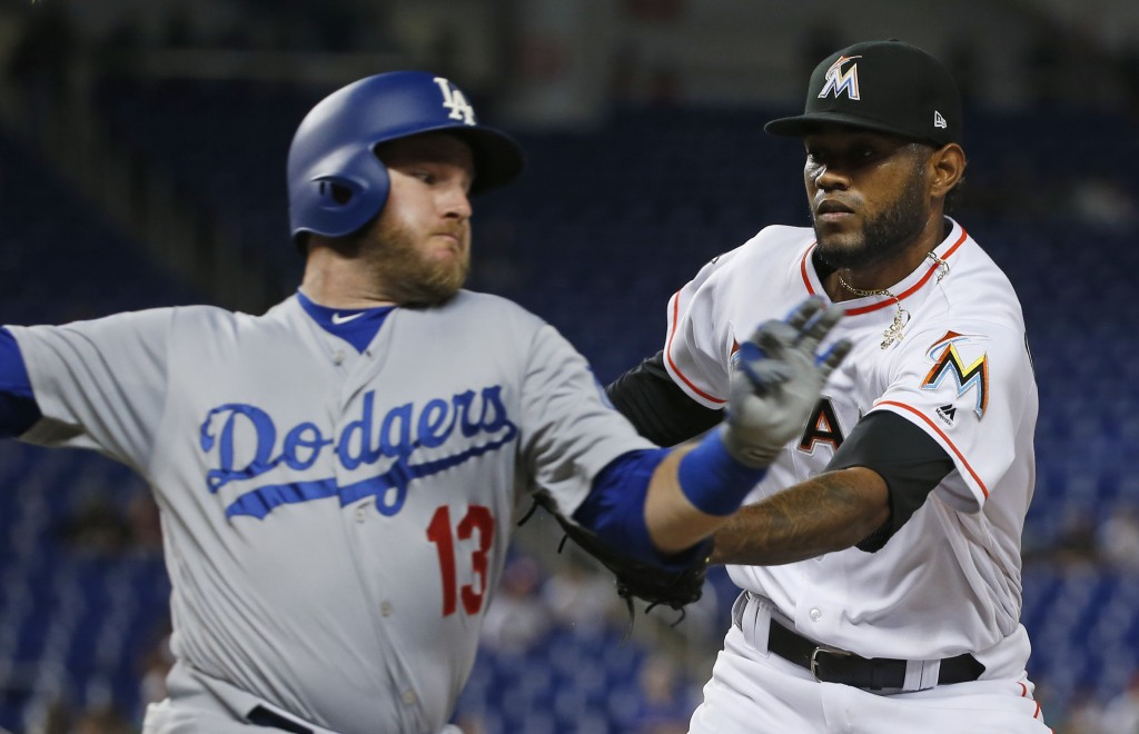 Miami Marlins relief pitcher Tayron Guerrero, right, tags out Los Angeles Dodgers' Max Muncy as he heads for first base during the seventh inning of a