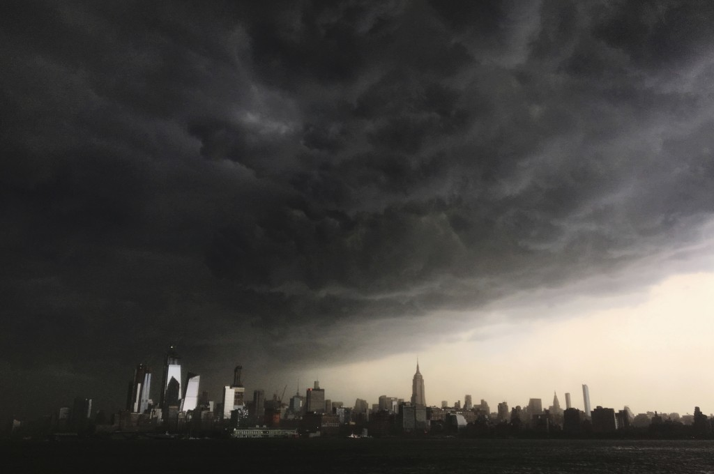In this Tuesday, May 15, 2018 photo, storm clouds gather over New York city seen from the Hudson River. A line of strong storms pushed across New York