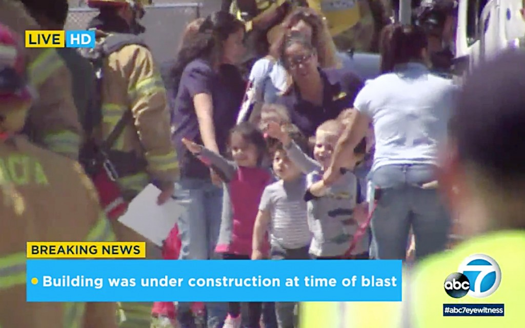 In this photo taken from video provided by KABC-TV, children are evacuated from a preschool across the street from a building that was rocked by an ex