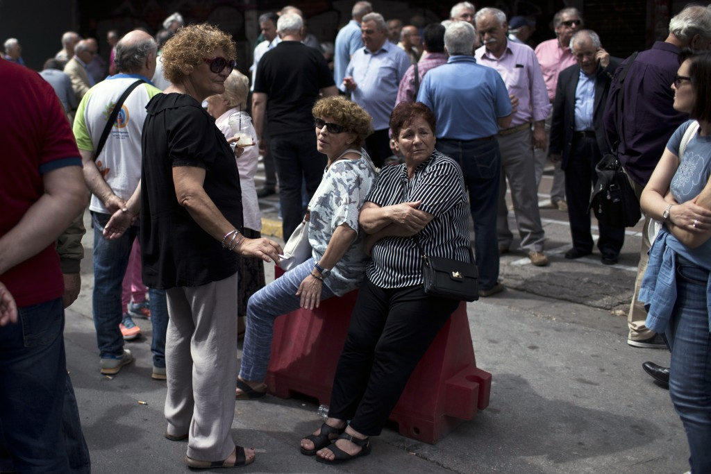 Pensioners take part in a protest outside the Labor ministry in central Athens, on Wednesday, May 16, 2018. The government has repeatedly cut pensions