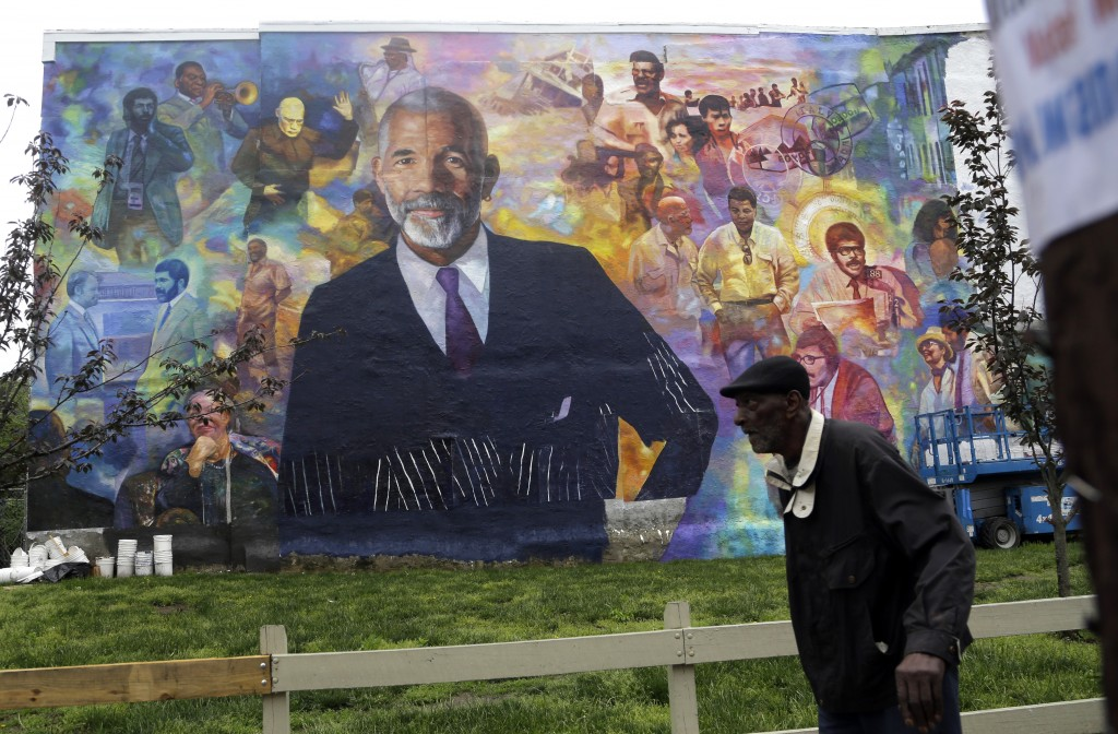 A pedestrian walks past a mural of journalist Ed Bradley, Wednesday, May 16, 2018 in Philadelphia. The mural, by artist Ernel Martinez, is in the Belm