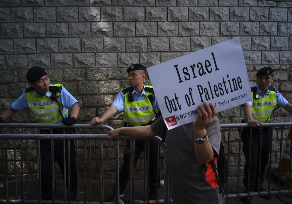 A protester displays a placard in front of police officers as they march outside the U.S. Embassy to condemn the Gaza Strip violence which left dozens