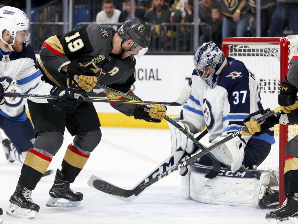 Winnipeg Jets goaltender Connor Hellebuyck, right, blocks a shot by Vegas Golden Knights right wing Reilly Smith during the second period of Game 3 of