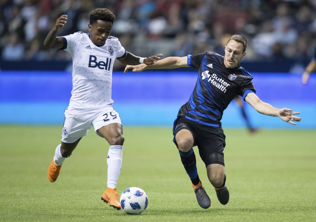 Vancouver Whitecaps' Yordy Reyna, left, beats San Jose Earthquakes' Francois Affolter to the ball and takes a shot on goal during the second half of a