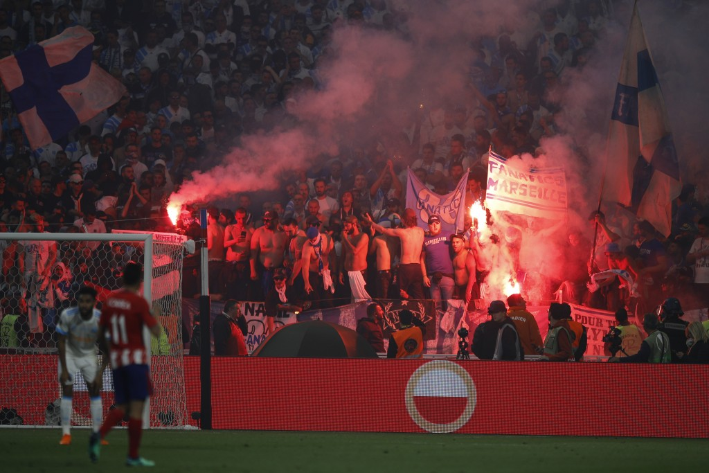 Marseille fans set off flares during the Europa League Final soccer match between Marseille and Atletico Madrid at the Stade de Lyon in Decines, outsi