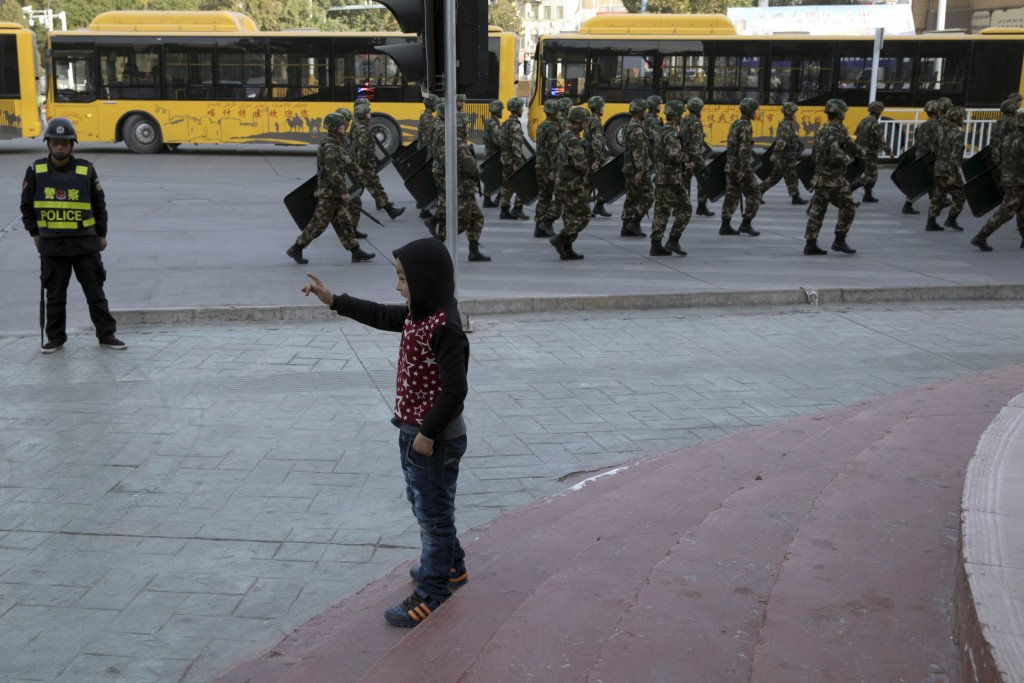 FILE - In this Nov. 5, 2017, file photo, a child reacts as security personnel march by in a show of force in Kashgar in western China's Xinjiang regio
