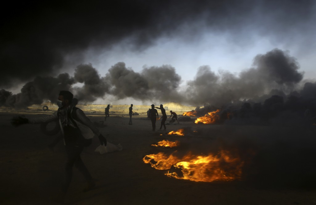 FILE - In this Tuesday, May 15, 2018 file photo, Palestinian protesters burn tires at the Gaza Strip's border with Israel, east of Khan Younis. The af