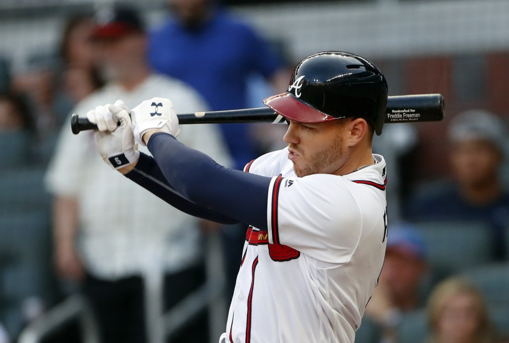 Atlanta Braves' Freddie Freeman drives in a run with a base hit during the first inning of the team's baseball game against the Chicago Cubs on Wednes