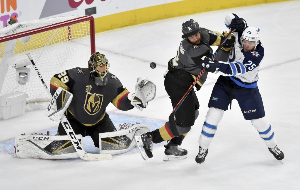Vegas Golden Knights goaltender Marc-Andre Fleury, left, and defenseman Deryk Engelland, middle, defend against Winnipeg Jets center Paul Stastny duri