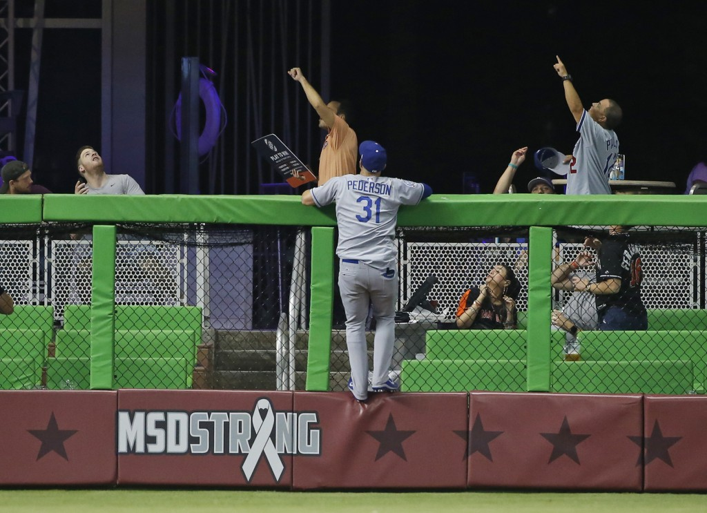 Los Angeles Dodgers left fielder Joc Pederson hangs on the fence as he watches a home run by Miami Marlins' J.T. Realmuto go into the stands during th