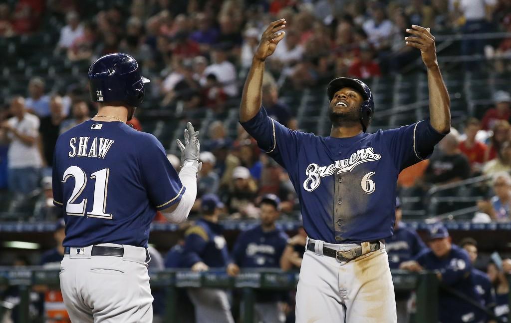 Milwaukee Brewers' Travis Shaw (21) celebrates his two-run home run against the Arizona Diamondbacks with teammate Lorenzo Cain (6) during the first i