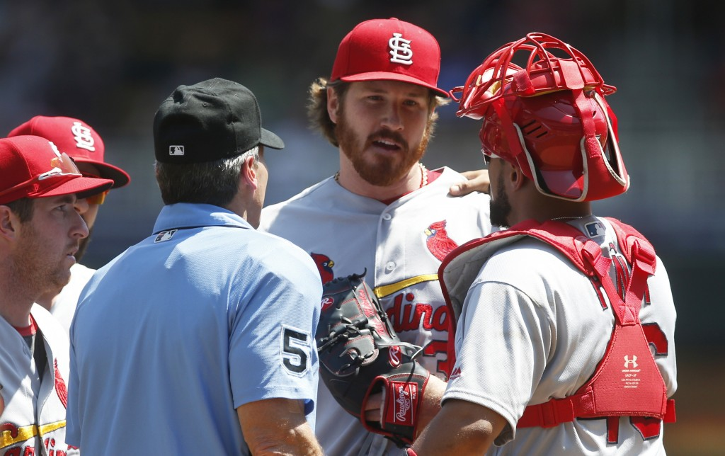 St. Louis Cardinals' pitcher Miles Mikolas, center, gets checked on in the second inning of a baseball game against the Minnesota Twins, Wednesday, Ma...
