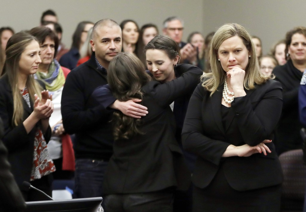 FILE - In this Jan. 24, 2018, file photo, former gymnast Rachael Denhollander, center, is hugged after giving her victim impact statement during the s