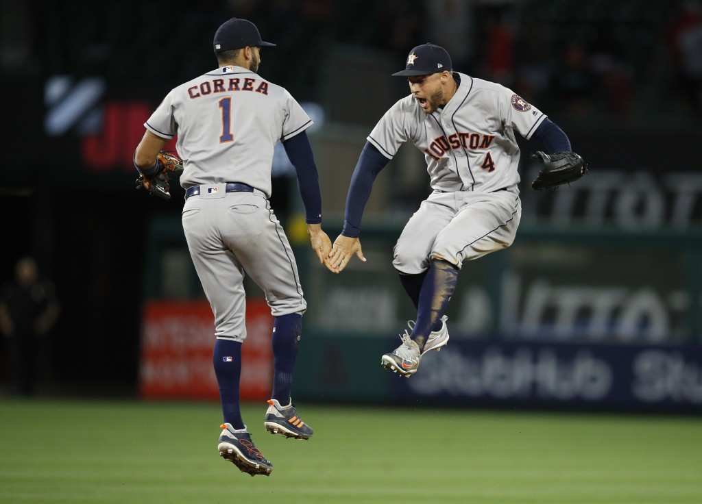 Houston Astros' Carlos Correa, left, and George Springer celebrate the team's 2-0 win over the Los Angeles Angels in a baseball game Wednesday, May 16
