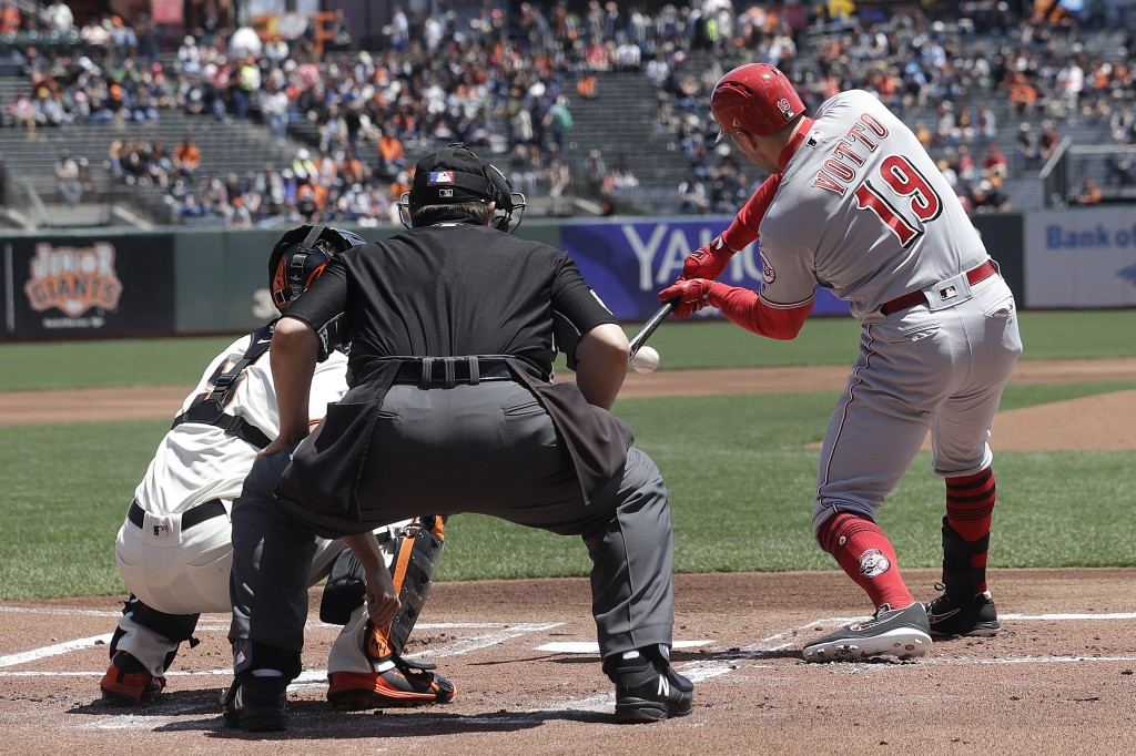 Cincinnati Reds' Joey Votto, right, hits an RBI-single against the San Francisco Giants during the first inning of a baseball game in San Francisco, W