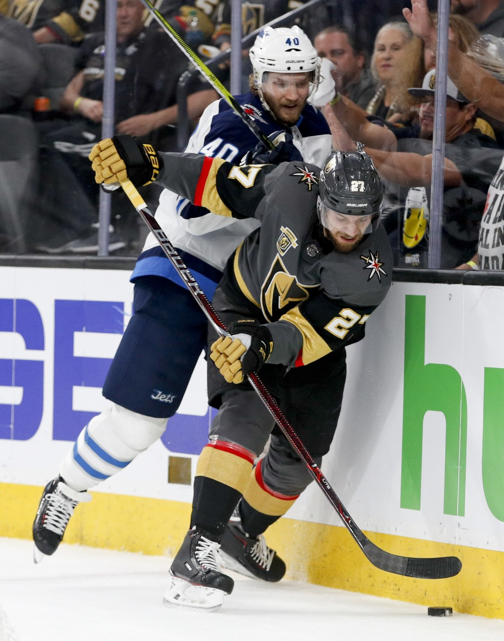 Vegas Golden Knights defenseman Shea Theodore, right, knocks the puck away from Winnipeg Jets right wing Joel Armia during the third period of Game 3