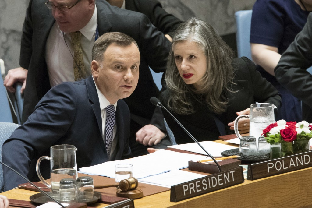 Polish President Andrzej Duda, left, speaks to a U.N. official during a Security Council meeting on international peace and security, Thursday, May 17