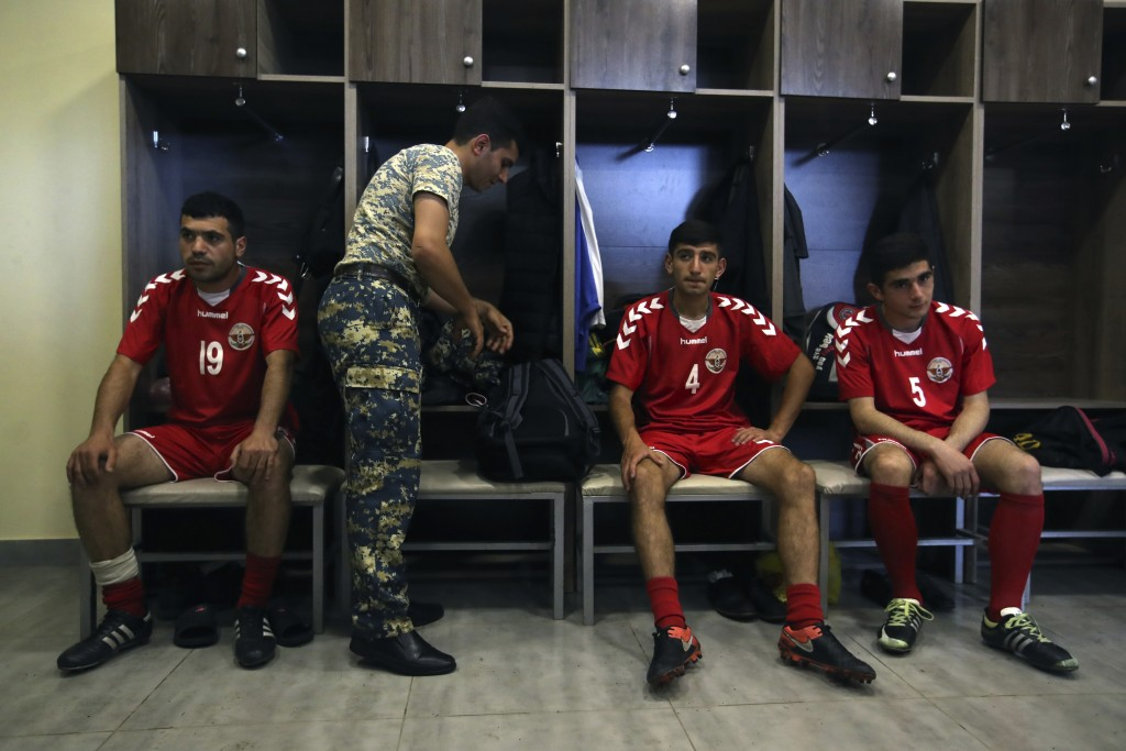 In this Friday, May 11, 2018 photo, an army officer prepares for training as his teammates listen to the coach of the soccer national team of the self