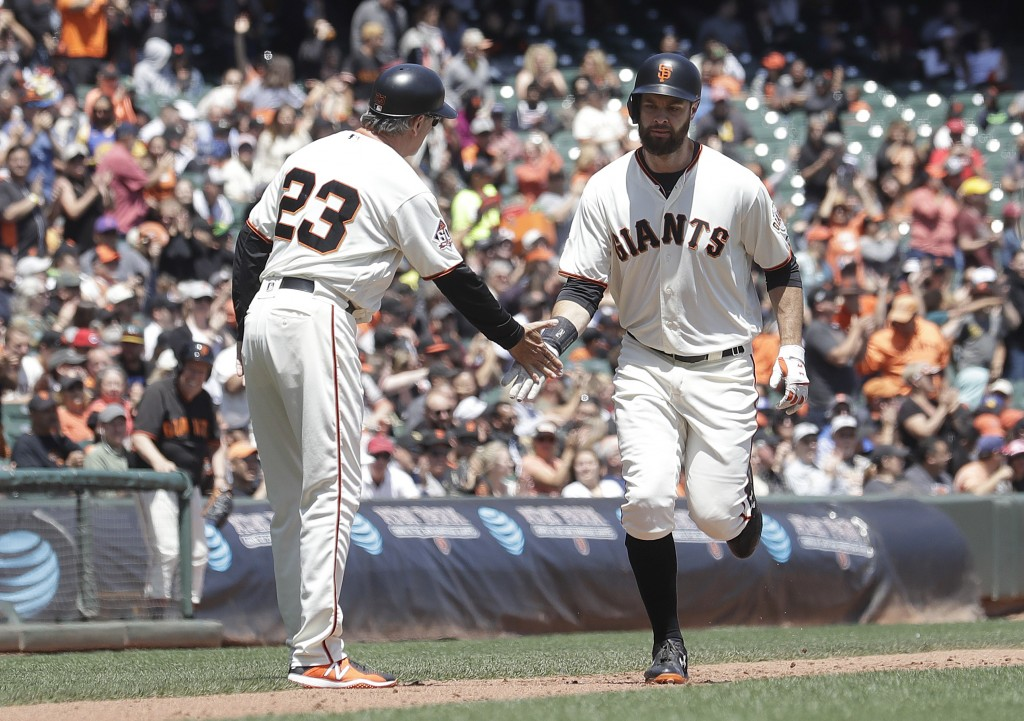 San Francisco Giants' Brandon Belt, right, is congratulated by third base coach Ron Wotus (23) after hitting a home run against the Cincinnati Reds in