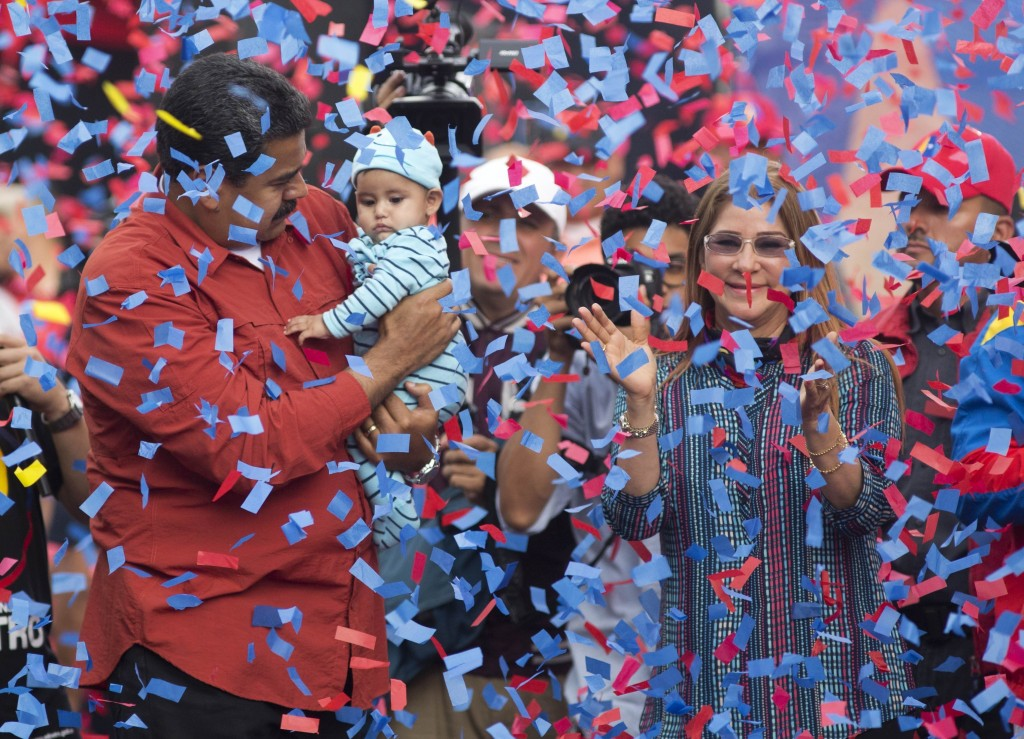 FILE - In this May 4, 2018 file photo, Venezuela's President Nicolas Maduro holds a baby as first lady Cilia Flores applauds during a campaign rally,