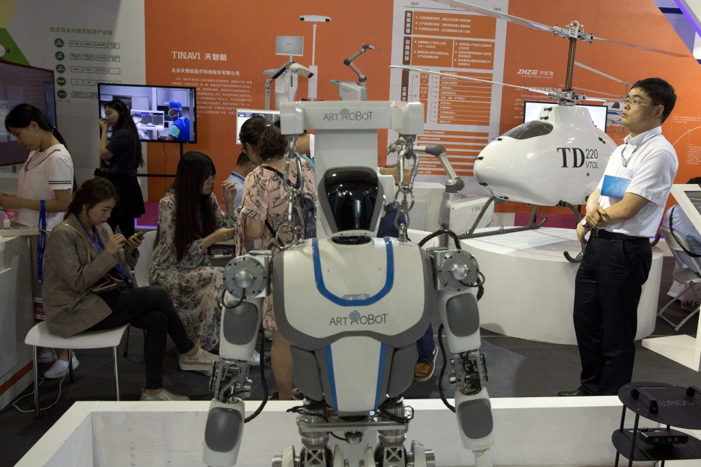 Visitors to the 21st China Beijing International High-tech Expo look at robots and helicopter drone displayed in Beijing, China, Thursday, May 17, 201