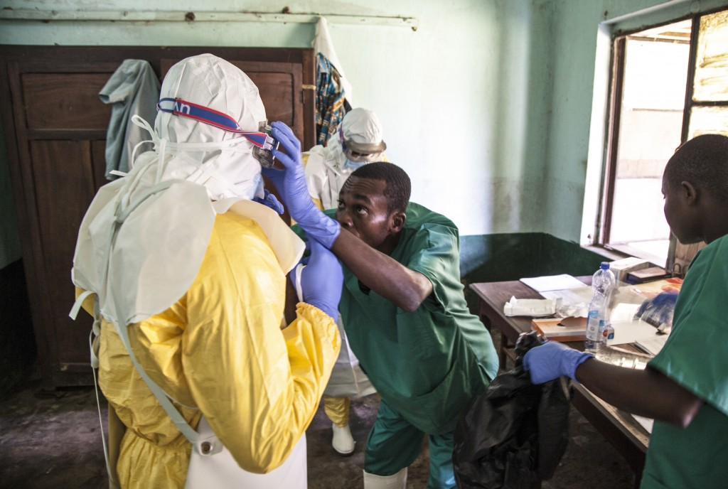 In this photo taken Saturday, May 12, 2018, health workers don protective clothing as they prepare to attend to patients in the isolation ward to diag...