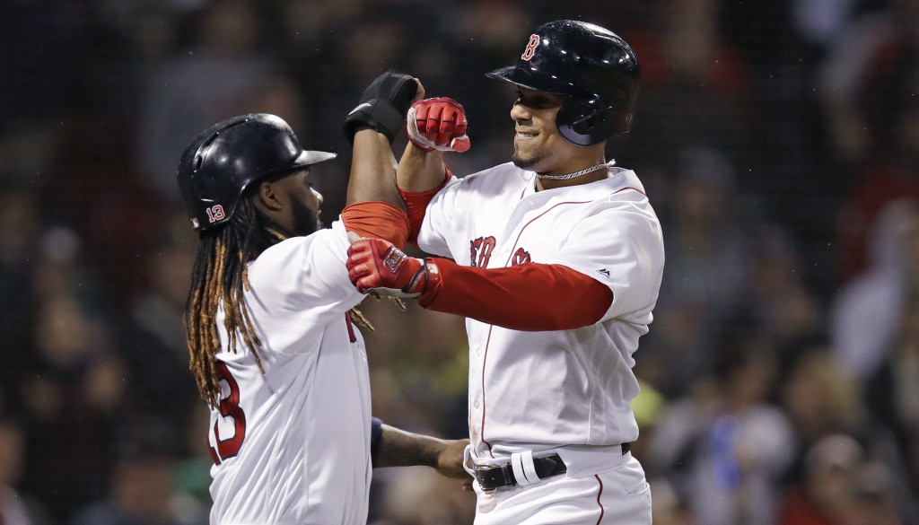 Boston Red Sox's Xander Bogaerts, right, is congratulated by Hanley Ramirez after crossing home plate on his three-run home run off Oakland Athletics