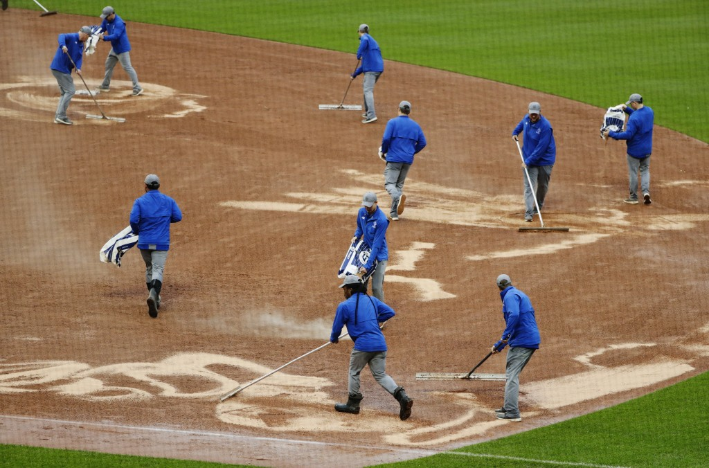 Grounds crew members work on the infield during the fifth inning of a baseball game between the New York Mets and the Toronto Blue Jays, Wednesday, Ma