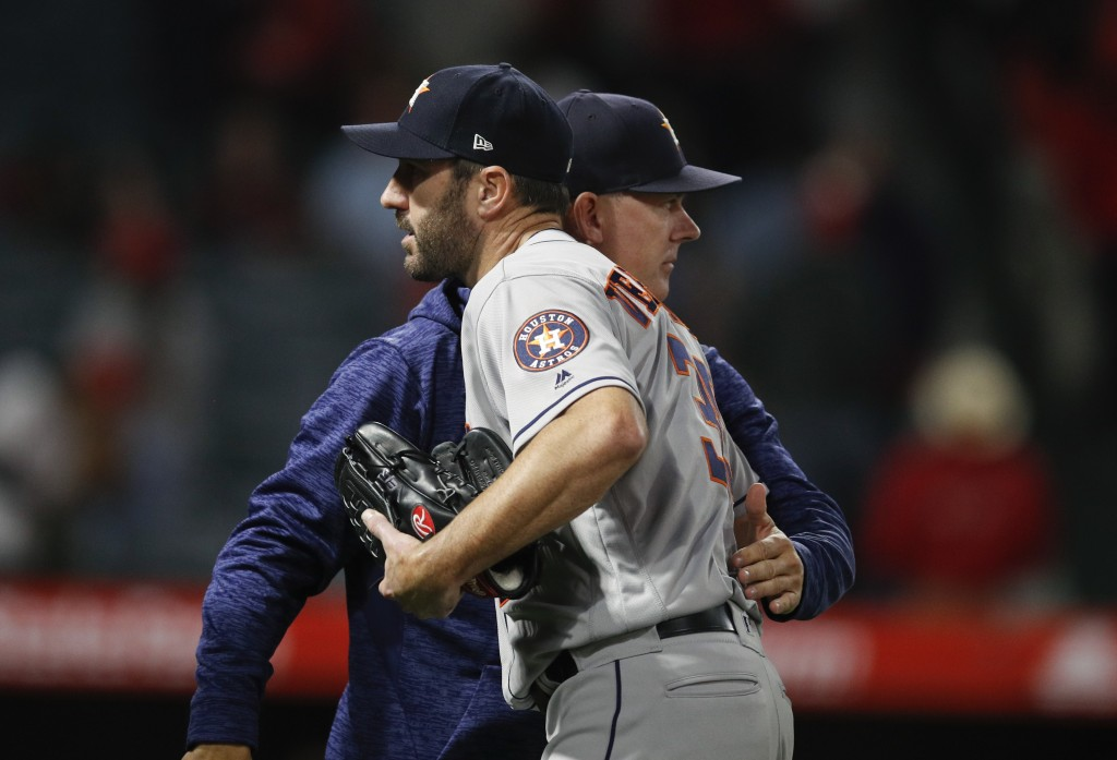 Houston Astros starting pitcher Justin Verlander gets a pack on the back from manager AJ Hinch after the team's 2-0 win over the Los Angeles Angels in...